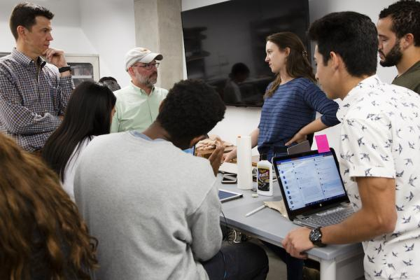 design students and faculty standing around a table during class